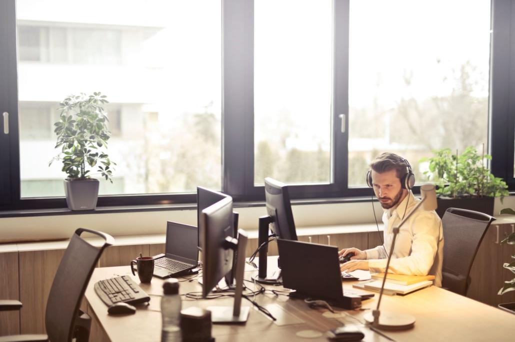 Junger Mann mit Kopfhörer am Schreibtisch sitzend vor einem Bildschirm